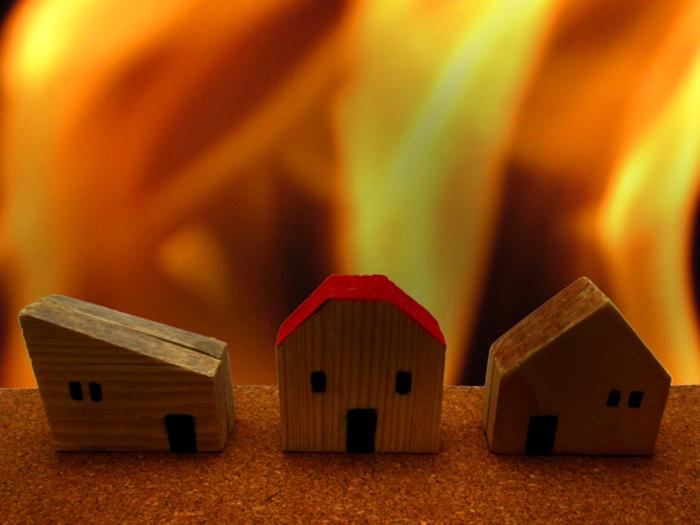 炎にさらされる家の模型